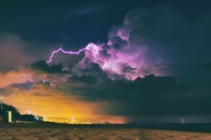 A lightning storm over a beach and distant city. The sky is purple and orange.