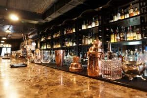 A shiny, modern bar with spirits lined up behind it