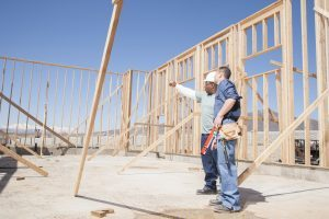 Two tradesmen in the frame of a building under construction