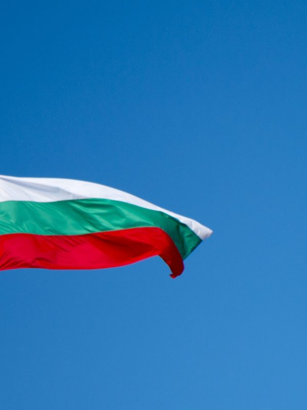 A Bulgarian flag on a mast, waving in the wind, against a blue sky
