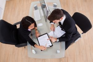 Two people in an office with a contract