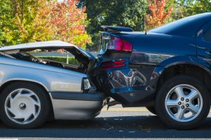 The aftermath of a car crash - a silver car has rear-ended a blue car.