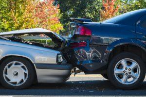 The aftermath of a car crash - a silver car has rear-ended a blue car.