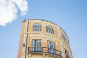 A curved, Spanish building in Malaga, standing alone against a blue sky
