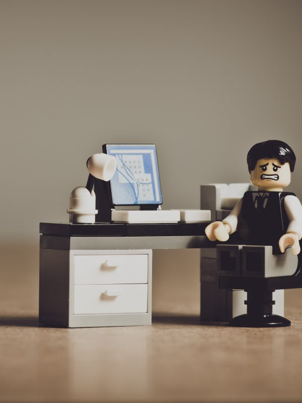 A lego businessman at his desk, grimacing at the camera