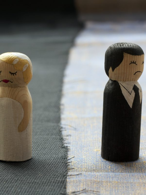 Two figurines - a bride and a groom - face away from each other, with angry faces