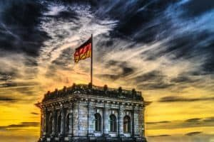 A tower on the Reichstag with a German flag flying against the sunset