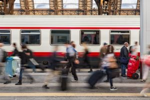 A platform at Milan train station, with people walking along. A train is pulling in.