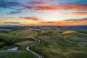 A winding road over low hills in San Quirico d'Orcia. It is sunset.