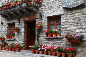 A rural Spanish restaurant frontage with many flowerpots.