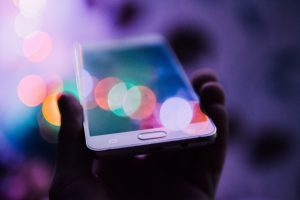 A smart phone being held up, reflecting coloured lights