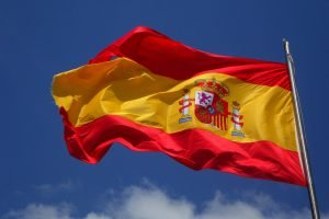 A Spanish flag waving in the wind against a blue sky