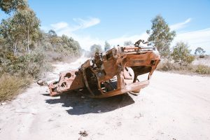 Upside-down, burnt-out car. It has been in a bad accident.