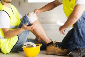 A workman with an injured knee being treated by a colleague