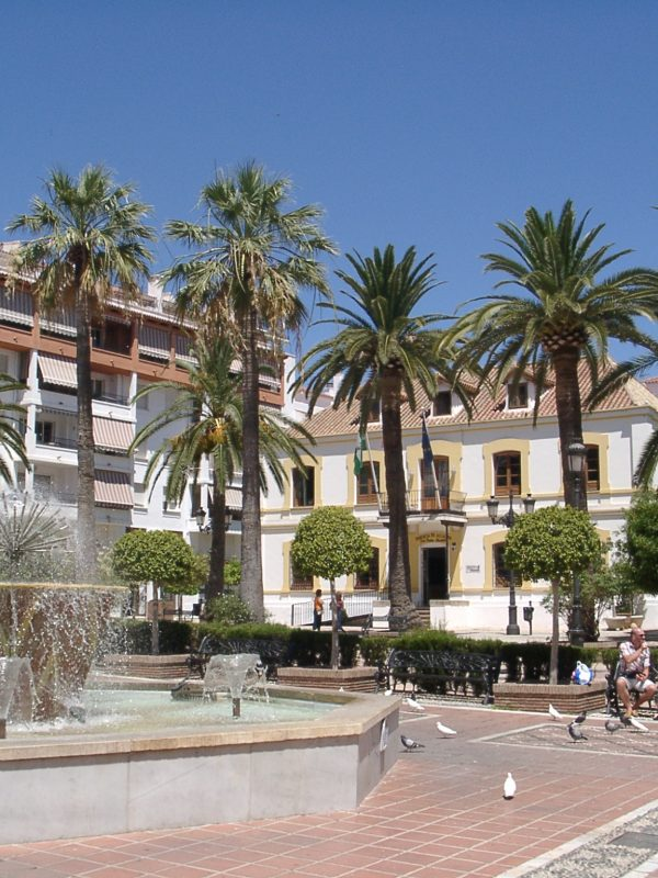 San Pedro de Alcántara - the plaza. A fountain surrounded by palm trees and white buildings