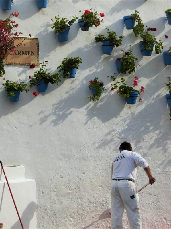 Flower pots attached to a white wall in Marbella. A man is repainting the wall.