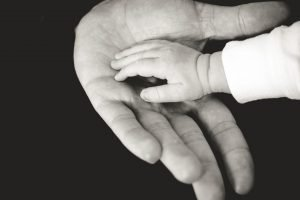 a black and white photograph of a babys hand resting in an adults