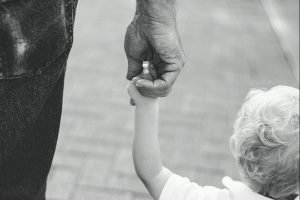 A black and white picture of a child holding an older adults hand