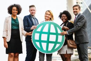 Group of people holding a cut-out of a globe