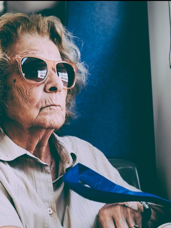 an elderly woman on the bus, wearing sunglasses