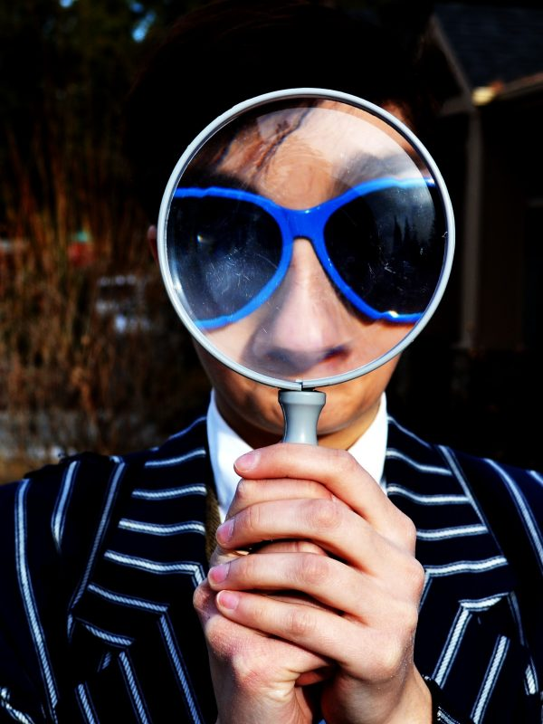 Man holding a magnifying glass to his face
