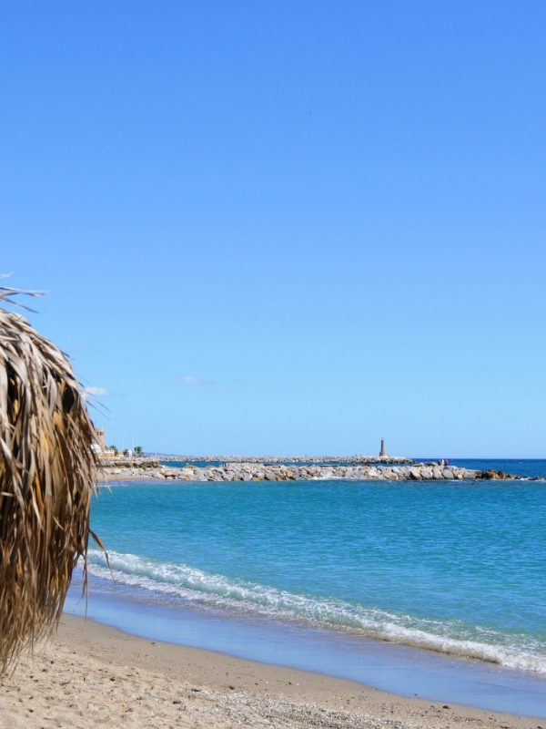 Playa de Nueva Andalucía - the side of a straw umbrella, some beach and calm blue sea