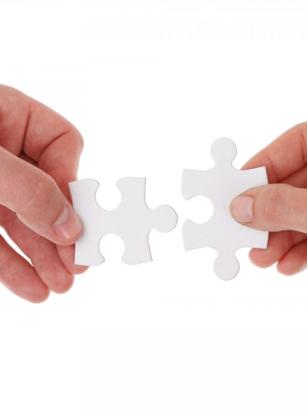 Two hands holding jigsaw pieces